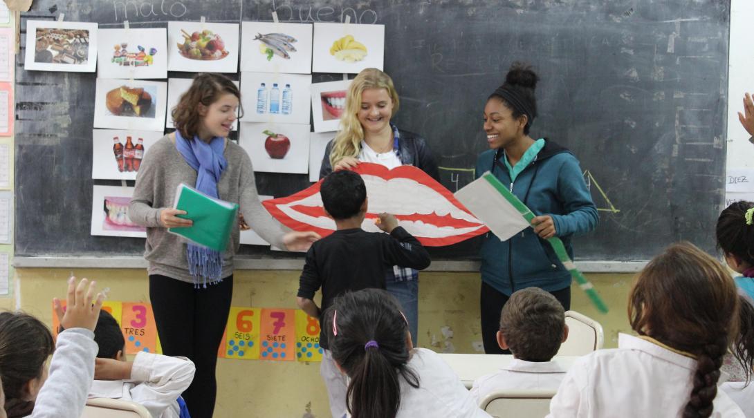 Durante su voluntariado para jóvenes, un par de voluntarias le explican a niños sobre higiene bucal.